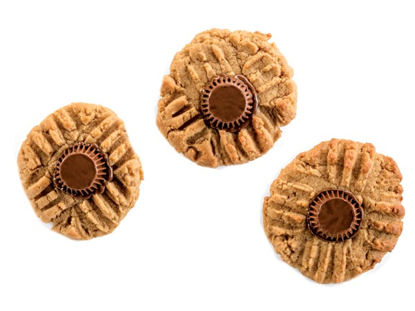 Three peanut butter cookies topped with a mini Reese's peanut butter cup