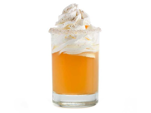 Sugar-rimmed glass of apple pie shooter garnished with whipped topping