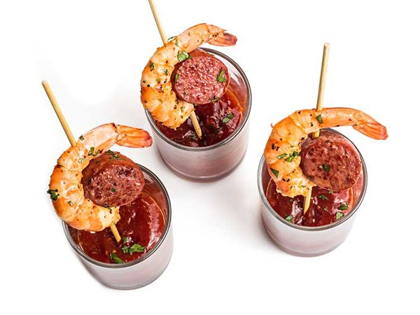 Three shrimp and sausage skewers each served in a cup of sauce