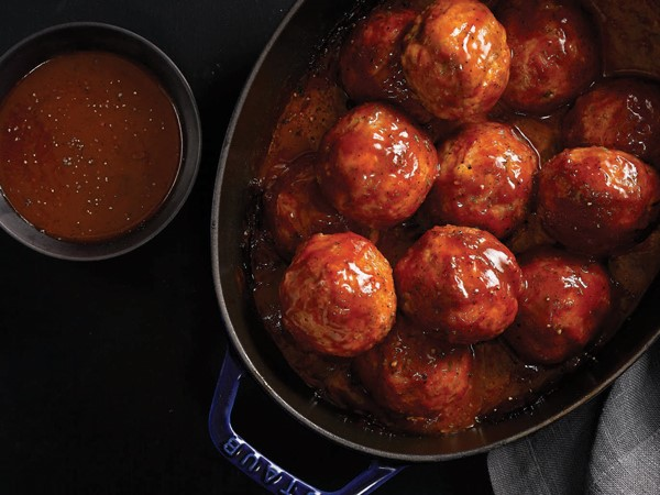 Pot of hamballs covered in sauce and served with a side of sauce
