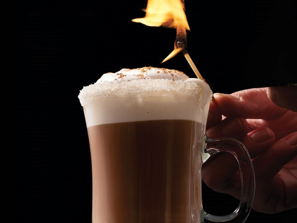 Glass of coffee topped with foam, whipped topping and cinnamon with a person holding a match above the glass