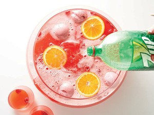 7UP poured into punch bowl with red punch and garnished with orange slices