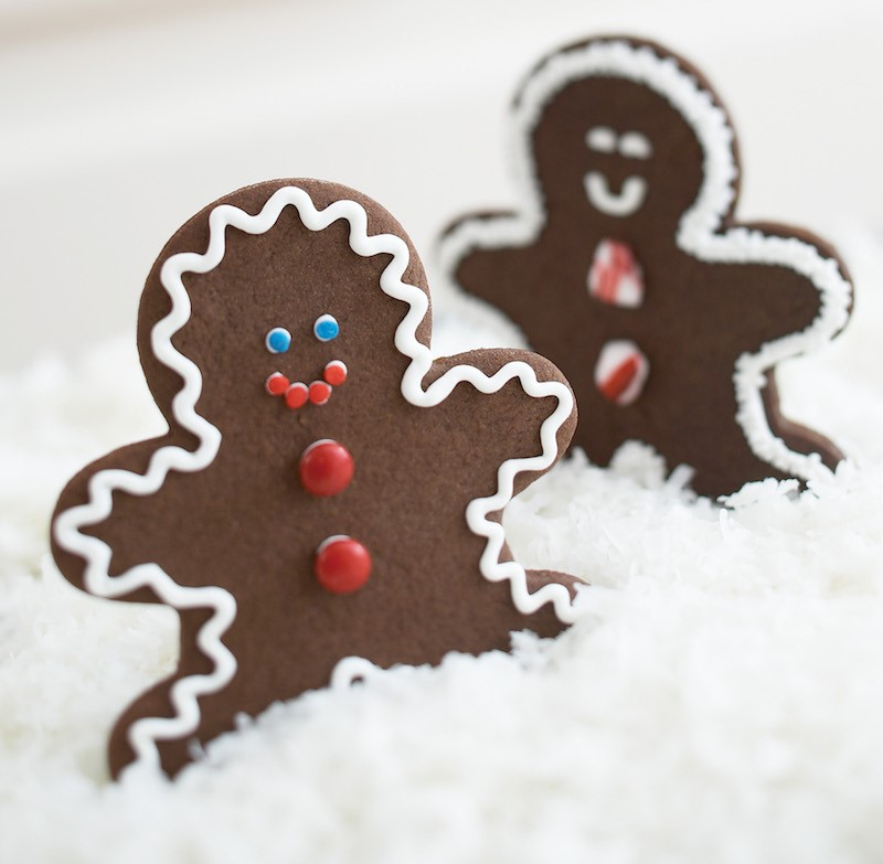 Two decorated ginger bread men on top of coconut flakes