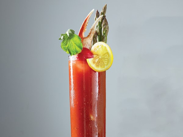 Tall glass of bloody mary, garnished with aspargus, crab leg, lemon slice, cherry tomato and celery stalk