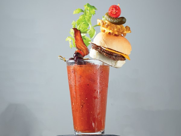 Glass of all-American bloody mary garnished with a cheeseburger, celery stalk, kalamata olives and bacon