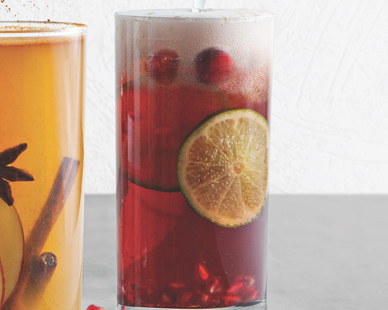 Holiday mimosa with pomegranate seeds, cranberries, and lime slices