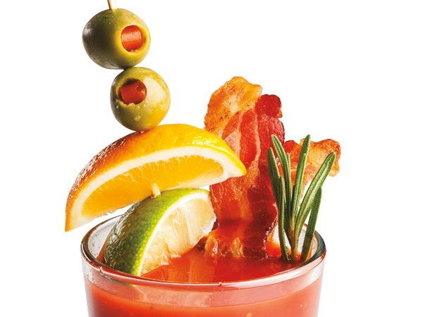 Glass filled with bloody mary, garnished with bacon slices, lime and orange wedges and stuffed olives