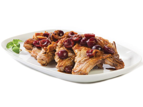 Platter of pork chops garnished with cherries and glaze