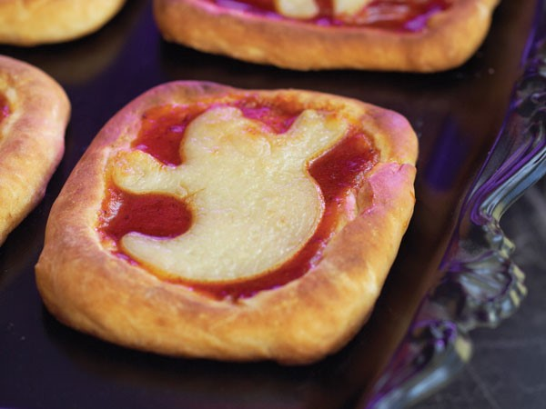 Mini rectangle pizzas topped with ghost-shaped pizza dough