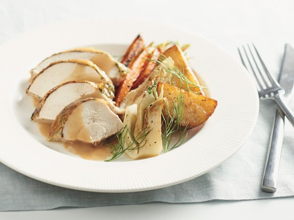 Sliced herb roasted chicken with roasted vegetables and homemade gravy