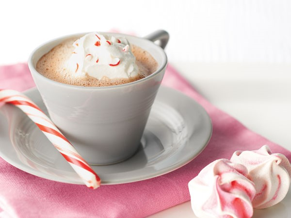 Cup of mocha topped with whipped topping and crushed candy cane, served with a candy cane