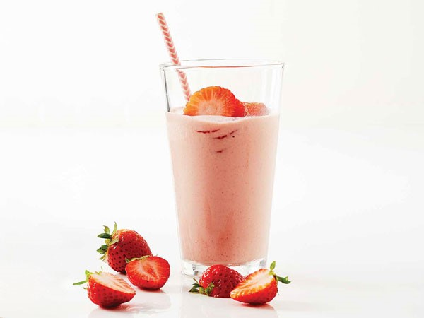 Glass of strawberry cherry workout smoothie garnished with strawberry slices and straw