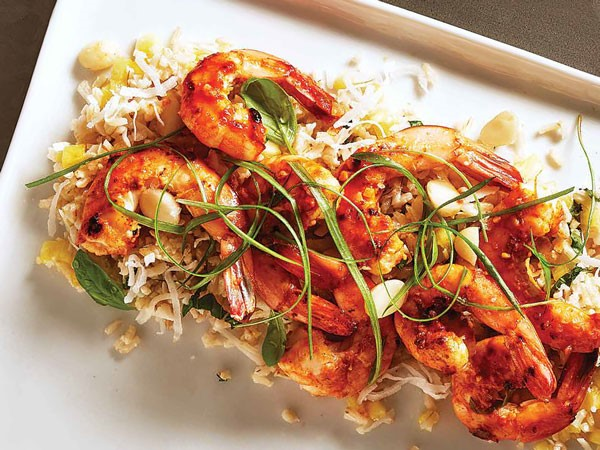 Hawaiian shrimp over coconut rice garnished with green onion strips