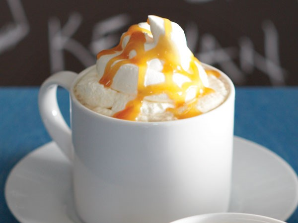 Mug of candy bar latte topped with whipped cream and caramel drizzle