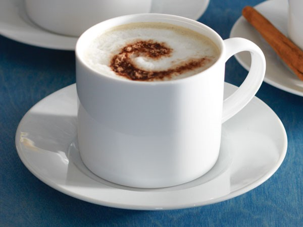 White mug of chocolate almond cafe topped with foam and cinnamon and served with a cinnamon stick