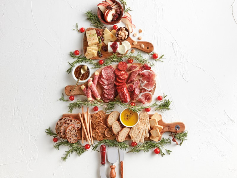 Tree made out of cutting boards, cheese, hard meats, rosemary, and fruits