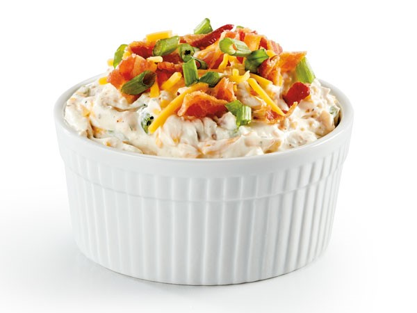 Small white bowl of dip topped with shredded cheddar cheese, bacon bits and chopped green onion