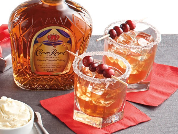Sugar-rimmed glasses of Christmas Old Fashioned, garnished with cranberries