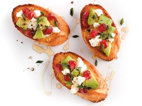 Crostini topped with avocado, feta and pomegranate