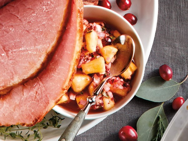 Sliced ham served with side of pineapple cranberry salsa