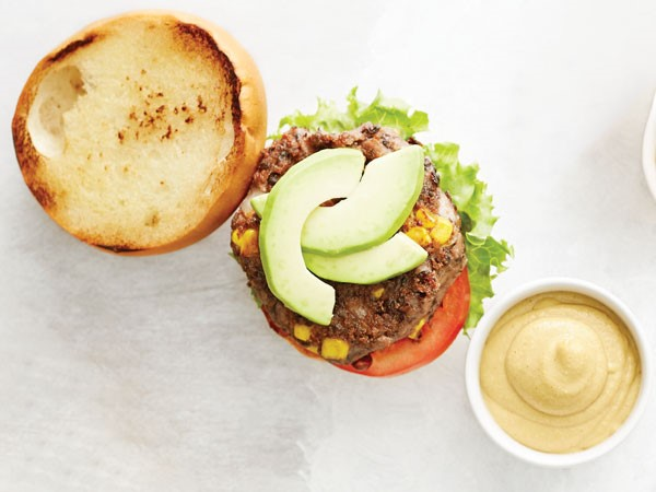Black bean burgers topped with avocado slices or caramelized onions on buns