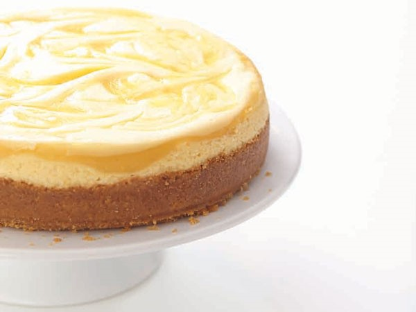 Graham cracker crust cheesecake topped with cream filling and a swirled lemon curd