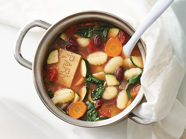 Pot of soup filled with gnocchi, vegetables and parmesan cheese