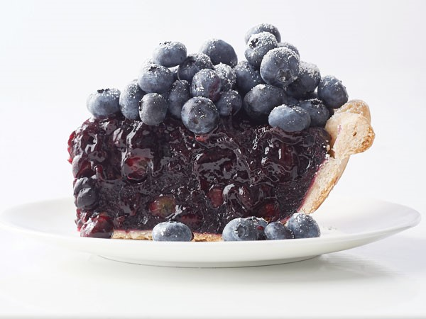 Slice of blueberry pie on a plate topped with fresh blueberries