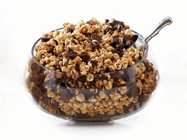 Glass bowl of peanut butter-flavored popcorn and Reese's mini peanut butter cups mixed and drizzled in chocolate