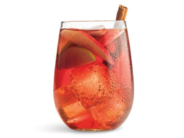 Glass of apple sangria with ice cubes, apple slices and a cinnamon stick