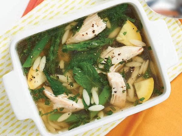 Pan of soup filled with orzo, squash, chicken, spinach and asparagus