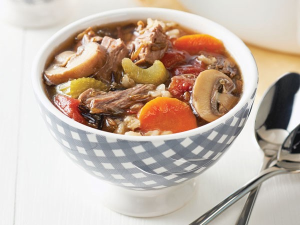 Hearty beef stew with celery, mushrooms, and carrots in soup bowl