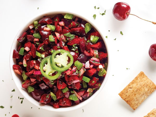 Bowl of sweet cherries mixed with red onion, cilantro and jalapeno