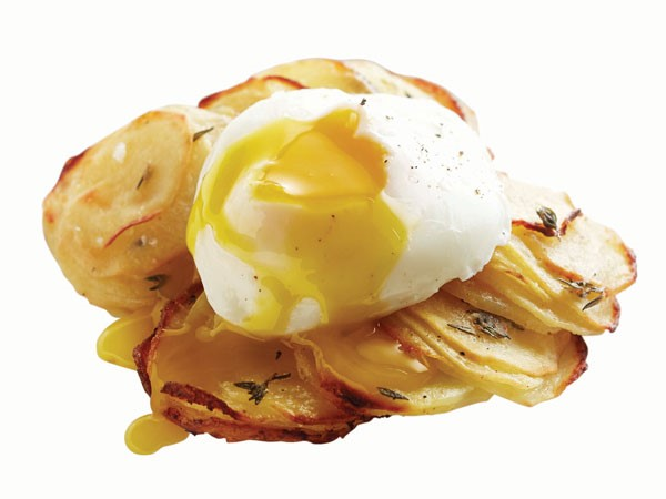 Sliced potatoes topped with poached egg
