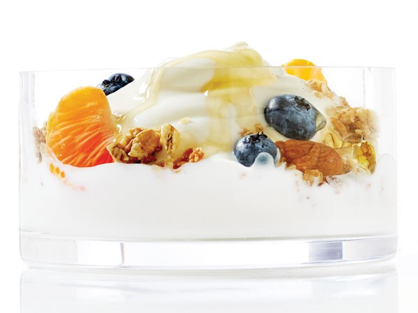 Bowl of yogurt topped with mixed nuts, oranges, honey and blueberries