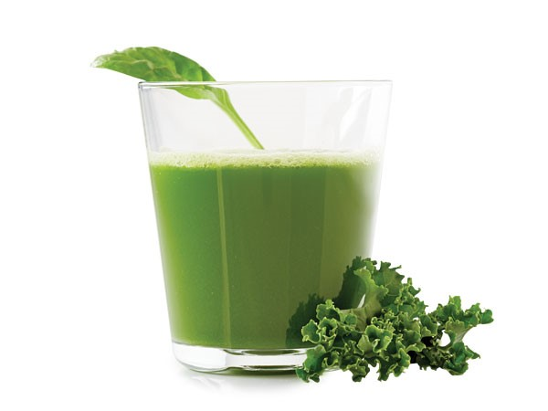 Glass of clean green, garnished with a spinach leaf