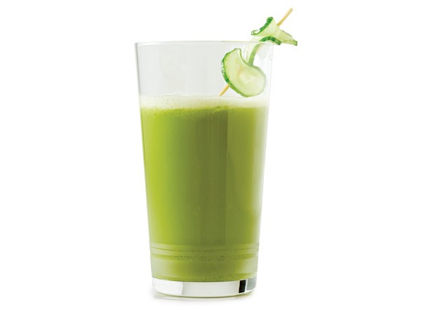 Glass of green liquid garnished with green apple slice