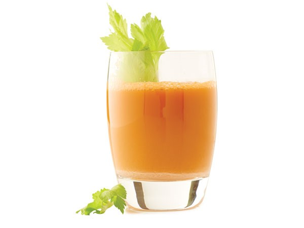 Glass of carrot crush garnished with celery stalk