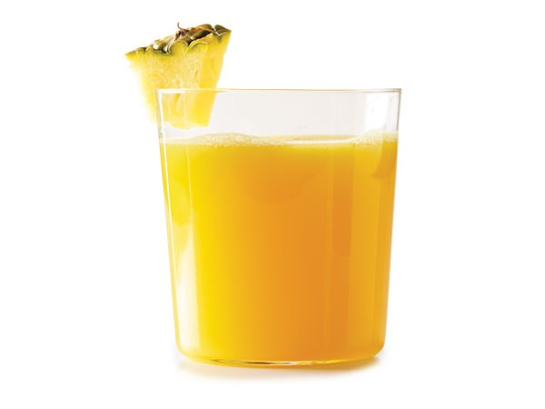 Glass of orange liquid garnished with a pineapple wedge