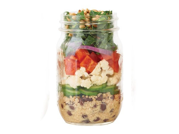 Mason jar layered with quinoa and beans, cucumber slices, cauliflower, bell pepper, red onion, kale and pine nuts