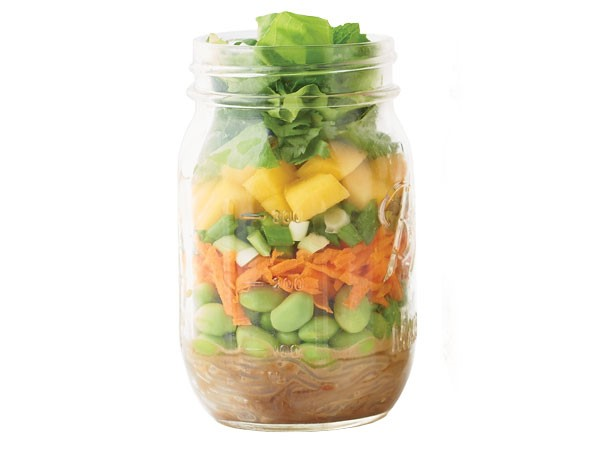 Glass jar layered with peanut butter, edamame, carrots, green onions, mango, lettuce and dressing