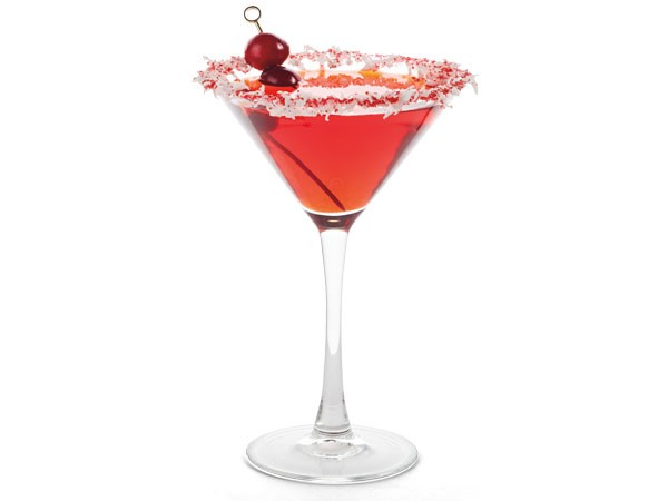 Coconut and sugar-rimmed martini glass filled with Christmas Cosmo, garnished with cranberries