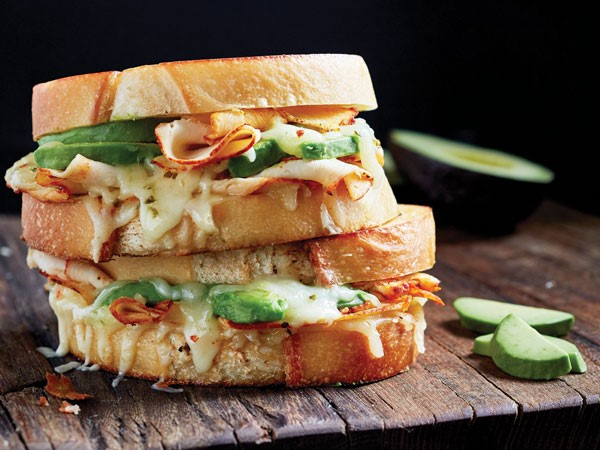 Two stacked buffalo chicken sandwiches with sliced turkey, avocado, melted cheese, and buffalo sauce