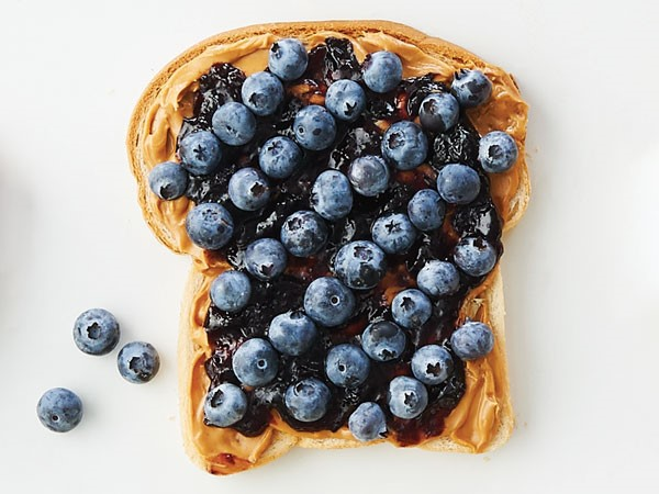 Bread topped with peanut butter, jelly, and fresh blueberries