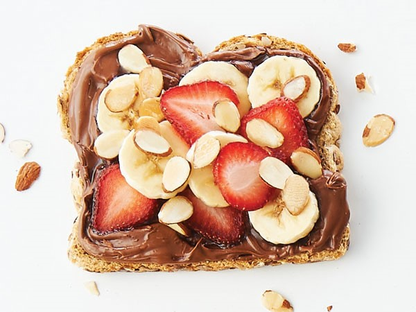 9-grain bread smothered in chocolate-hazelnut spread and topped with sliced bananas, strawberries and almonds