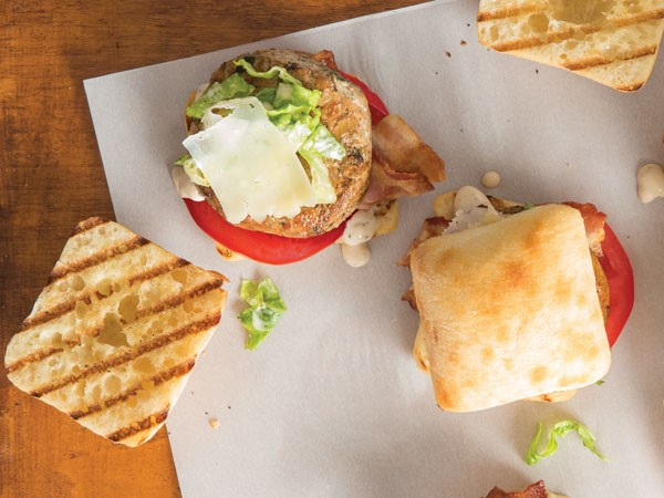 Grilled ciabatta rolls topped with chicken patty, lettuce, tomatoes, bacon and mozzarella shavings