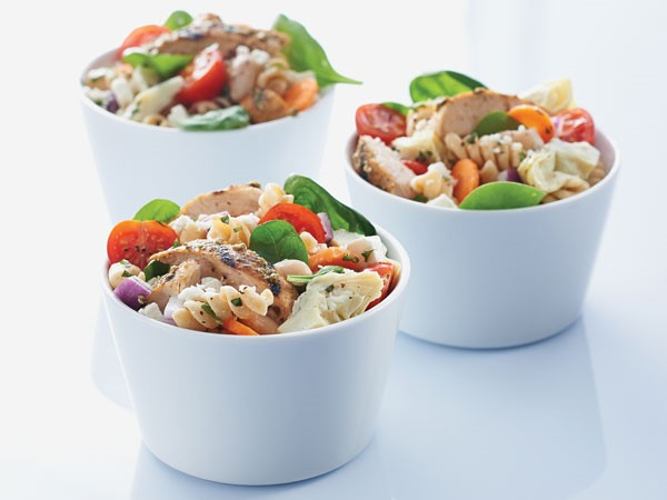 Small white bowls of chicken pasta salad with basil