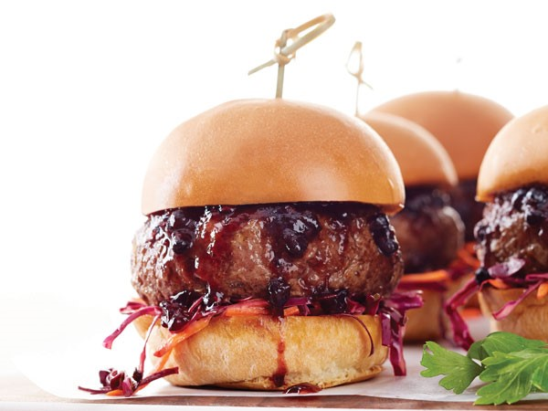 Burger patty topped with blackberry-bourbon sauce with slaw between a toasted slider bun
