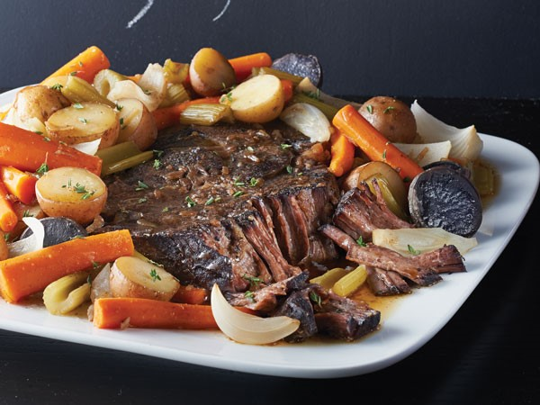 Pot roast surrounded by stewed vegetables on white platter
