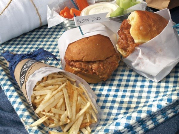 Sloppy joe sandwiches served with fries and vegetables on a blue-and-white checkered picnic blanket